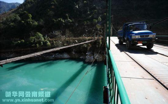 2月21日,车辆从贡山县的尼大当跨江大桥驶过,旁边的木质吊桥已经弃用.