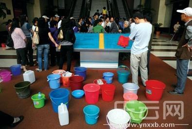 提着水桶,居民区政府打水.记者