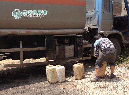 """""""条纹衫男子""""将装满柴油的塑料桶搬到另外一辆油罐车"""