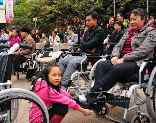 彝良贫困残疾人轮椅车发放仪式现场,一名小女孩正帮大人试坐轮椅车.