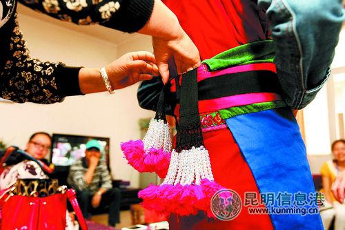 为女儿装扮上彝族传统服饰。 本版图片记者李海曦/摄
