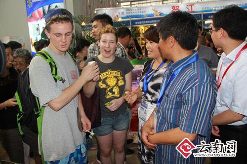 """国外客商在南博会现场品尝云南罗平""""甜园蜜语""""牌土蜂蜜"""