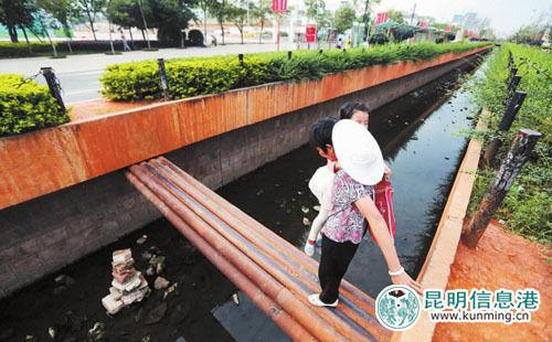 """一位老人抱着孩子通过钢管搭成的""""独木桥""""。记者张玉杰\摄"""