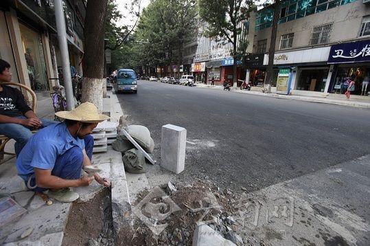 国防路上还有工人在修理路沿。记者 苏颖 摄