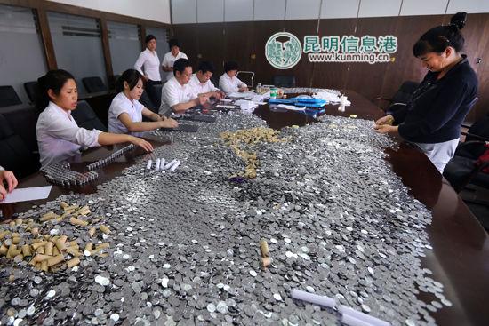 一角硬币在办公桌上堆了厚厚一层,银行工作人员清点硬币。张玉杰摄