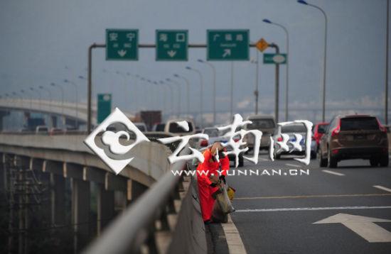 环卫工在高速路车流中捡垃圾 江洋 摄