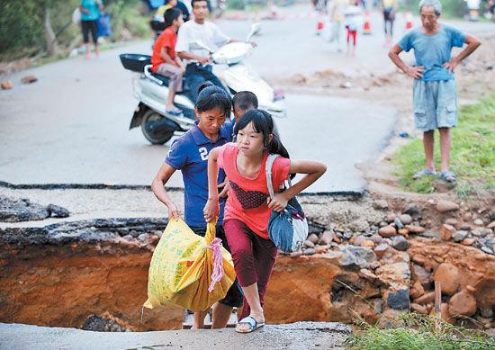 """受强台风""""尤特""""影响,8月20日,在桂平市金田镇,群众经过一处被冲毁的路段回家。新华社配图"""